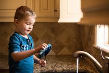 a boy washing dishes