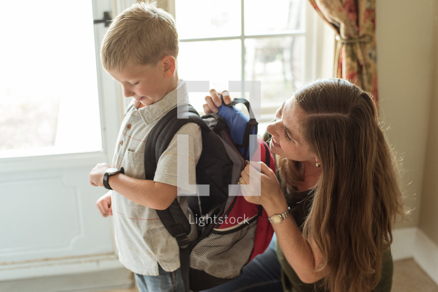 mother helping her son get ready for school