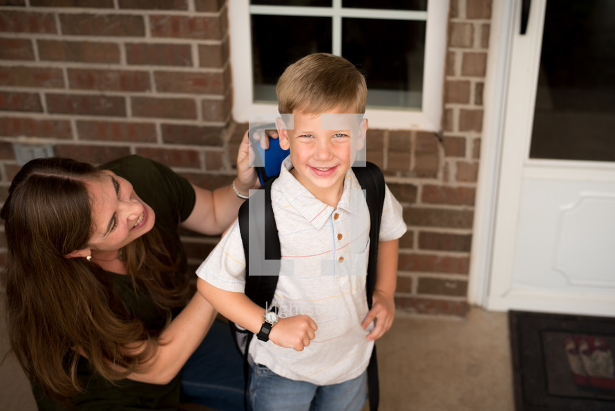 a mother helping her son get ready for school
