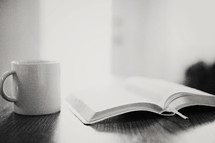 Morning light shining on a coffee cup next to an open Bible.