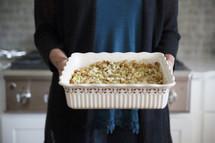 a woman holding a casserole