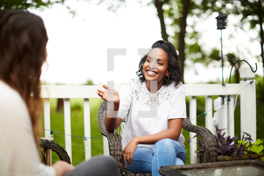 women talking on a patio