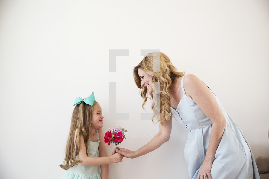 a daughter happily giving her mother flowers.