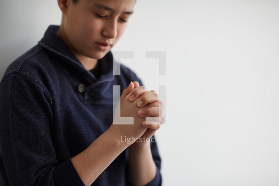 boy with head bowed in prayer