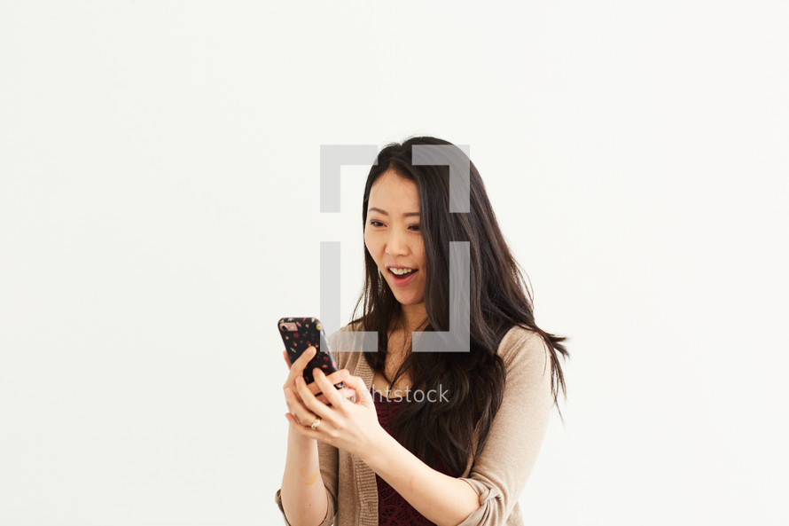 a woman looking at her cellphone and smiling