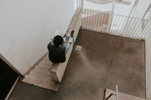 man reading a Bible in a stairwell