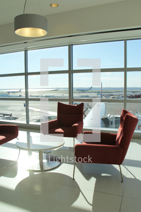 table and chairs and a view of the tarmac in an airport