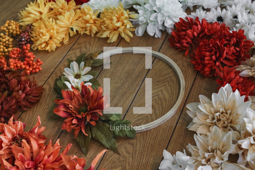 artificial fall flowers and wreath on a table