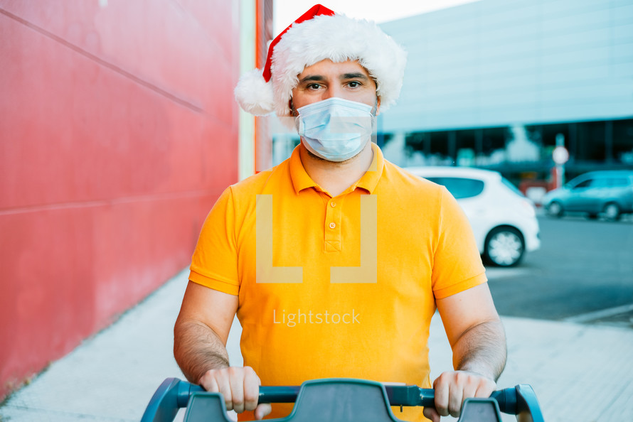 mature man with medical mask and christmas hat shopping.