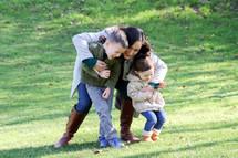 mother hugging her children