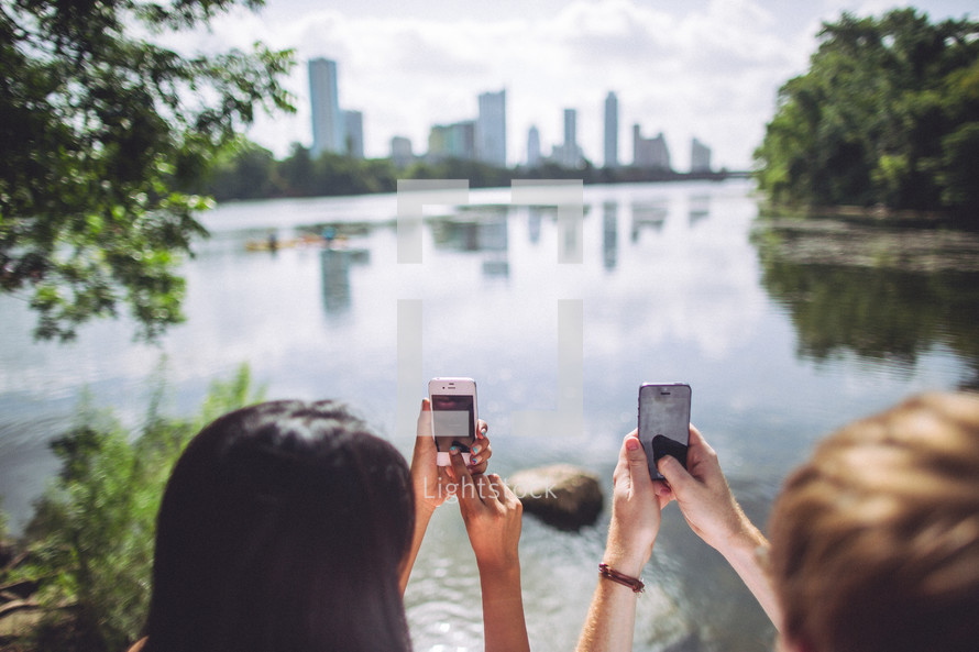 man and woman taking a picture with an iPhone