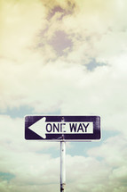 one way street sign against a sky