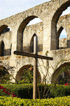 An old wooden cross stands in the stone courtyard and garden of a historic mission church, reminding visitors of the death and resurrection of Jesus Christ, along with the new life to be found in believing in Him.