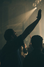 worshipers with hands raised during a worship service