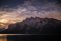 jagged mountain peaks and lake at sunset