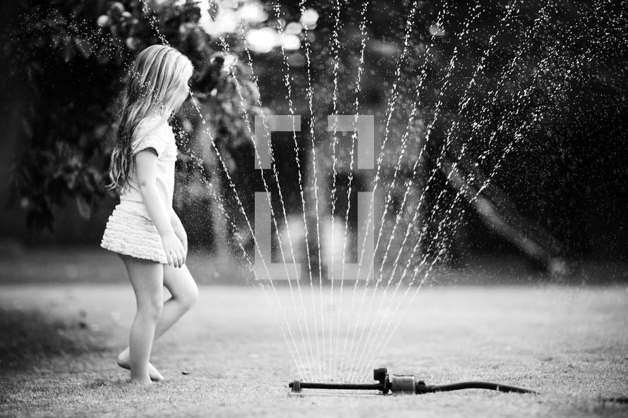 Girl playing in backyard water sprinkler during the summer.