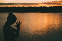 a woman meditating by a lake at sunset