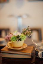 flowers in a tea cup on books