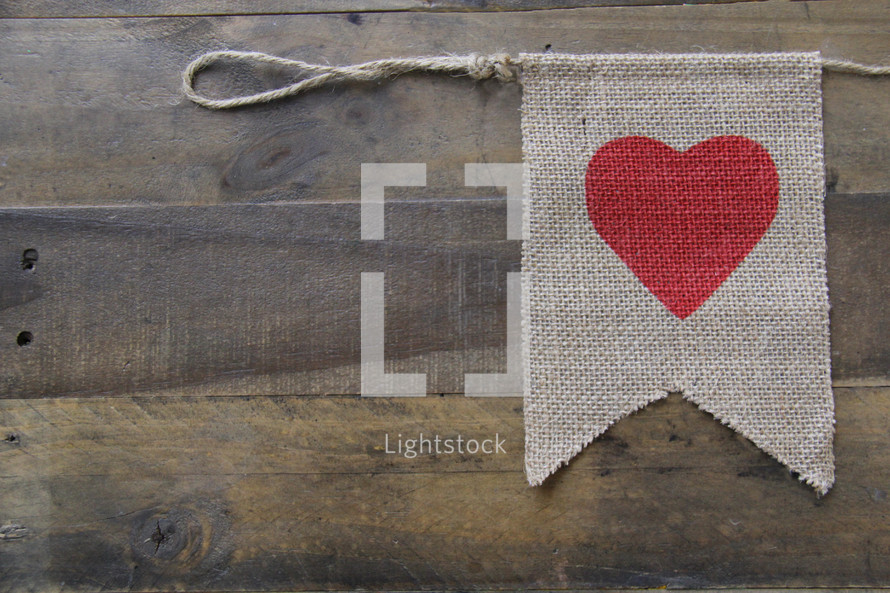 heart on a burlap banner against a wooden background