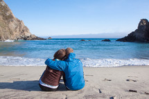 couple hugging sitting on a beach