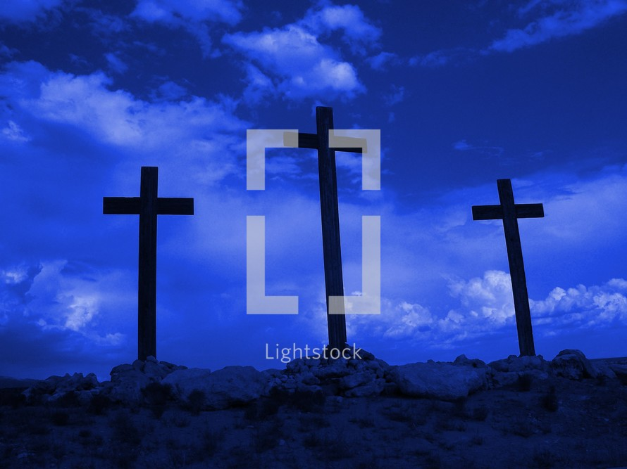 Three crosses of Calvary standing ominously against a dark blue sky
