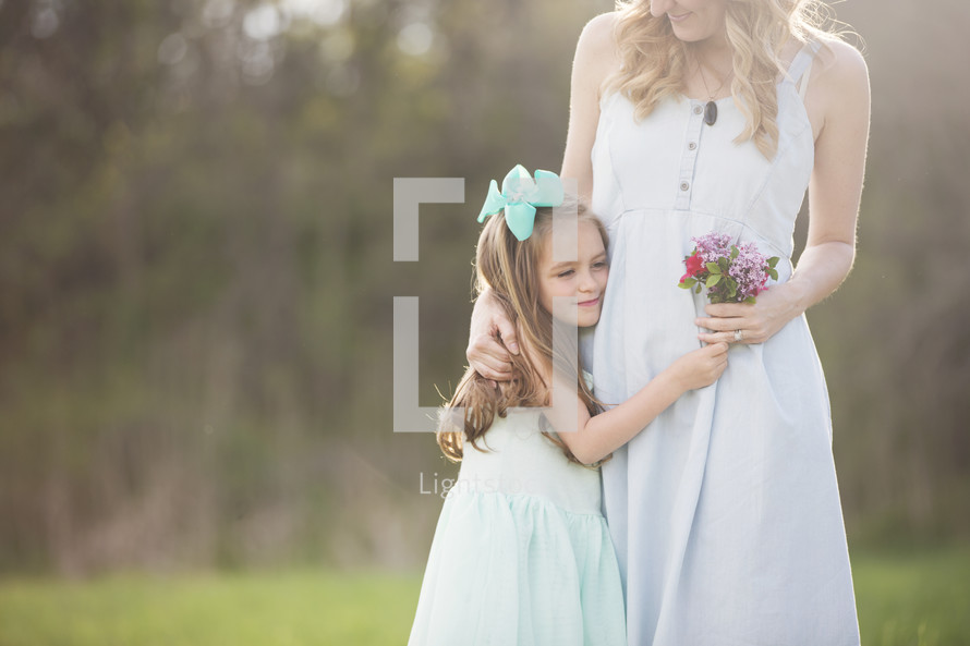 mother and daughter hugging with flowers outdoors