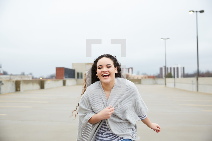 teen girl running in a parking deck