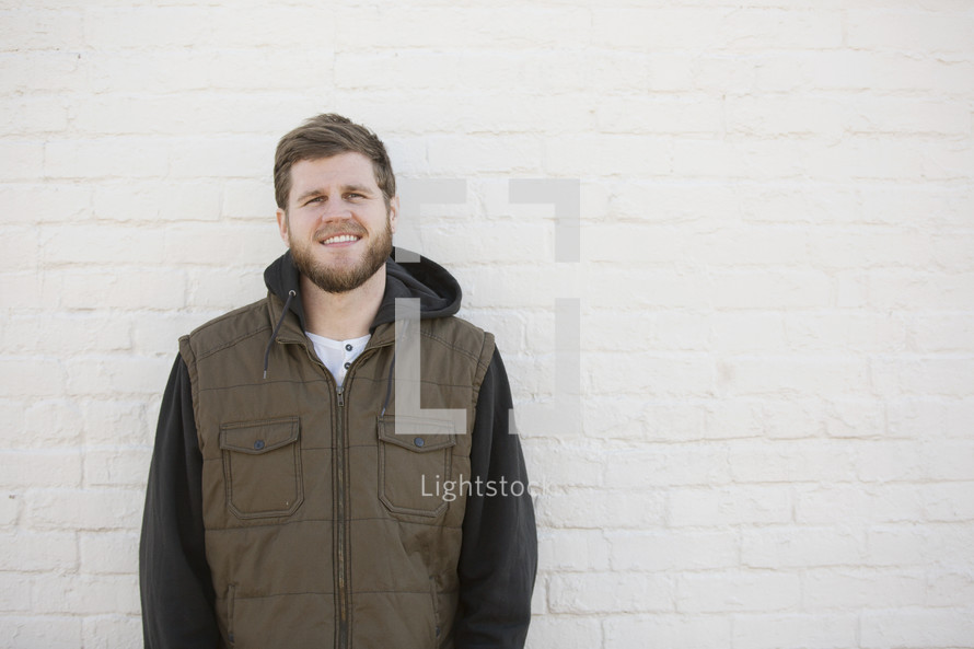 man standing against a white wall