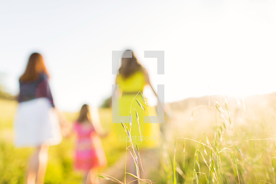Mother and daughters holding hands while walking through a sunny field.