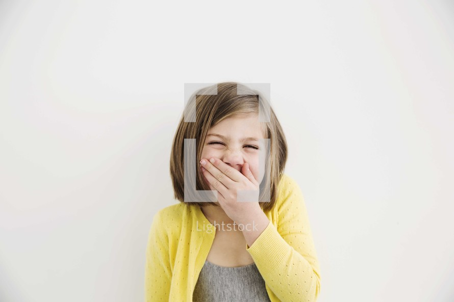 little girl covering her mouth while laughing.