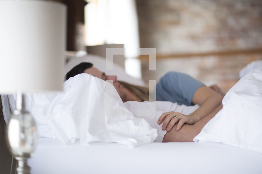 a couple lying in bed snuggling