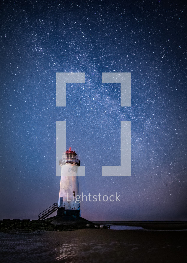 lighthouse under stars in the night sky