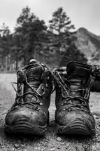 Muddy hiking boots on the ground.