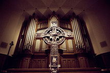 cross on an altar in front of organ pipes