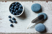stones, bowl of blueberries, and feather