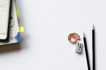 cellphone, notebook, pencils, pencil shavings, and pencil sharpener