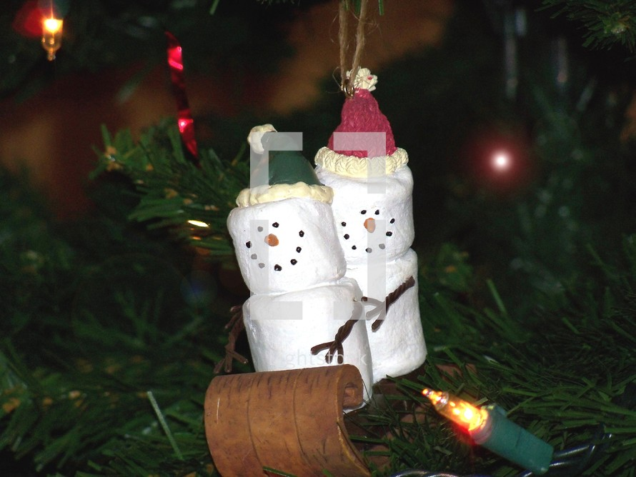 Christmas Marshmallow Sledding team - a male and female Marshmallow couple enjoy sleigh riding on a wooden sleigh in this decorative and whimsical Christmas tree ornament to help celebrate the Christmas holidays giving a fun and festive atmosphere.