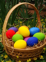 brightly colored Easter eggs in a basket outdoors
