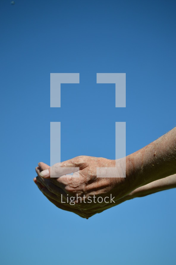 empty open cupped hands with dripping water in front of blue sky