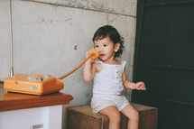 toddler girl talking on a vintage telephone