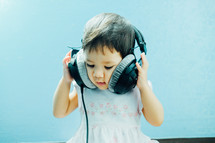 infant girl listening to headphones