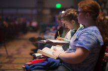 Teens taking notes at a conference.