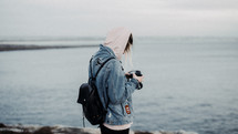 woman with a camera standing on a beach in fall