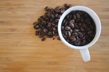 overhead view of a coffee cup filled with coffee beans