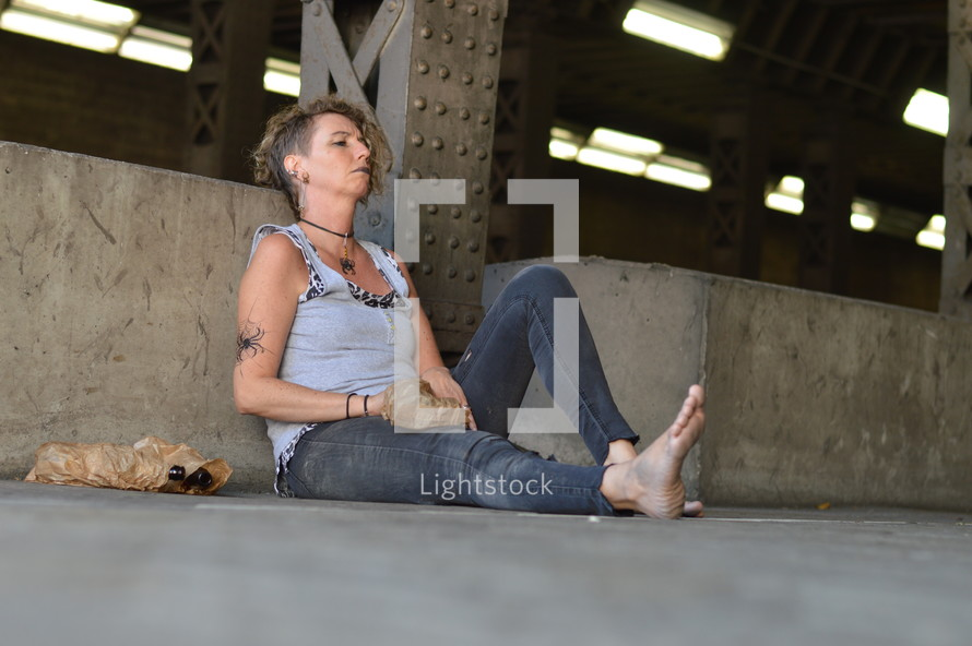 a woman sitting under a bridge with bottle of alcohol
