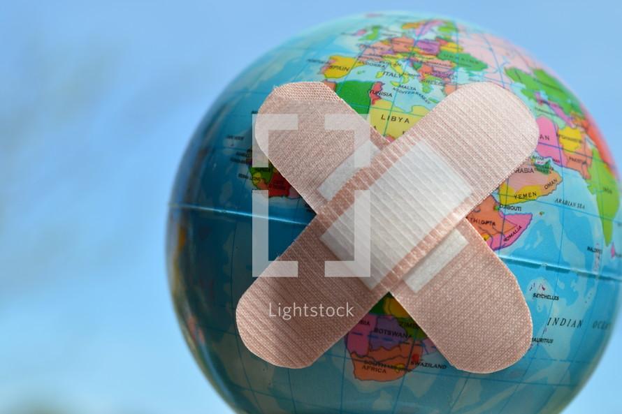 bandaids on a globe - healing the world