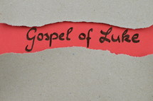Gospel of Luke - torn open kraft paper over light red paper with the name of the Gospel of Luke