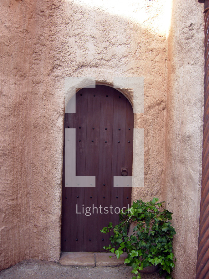 An arch shaped old wooden door like the kind you would see in the middle east during biblical times.