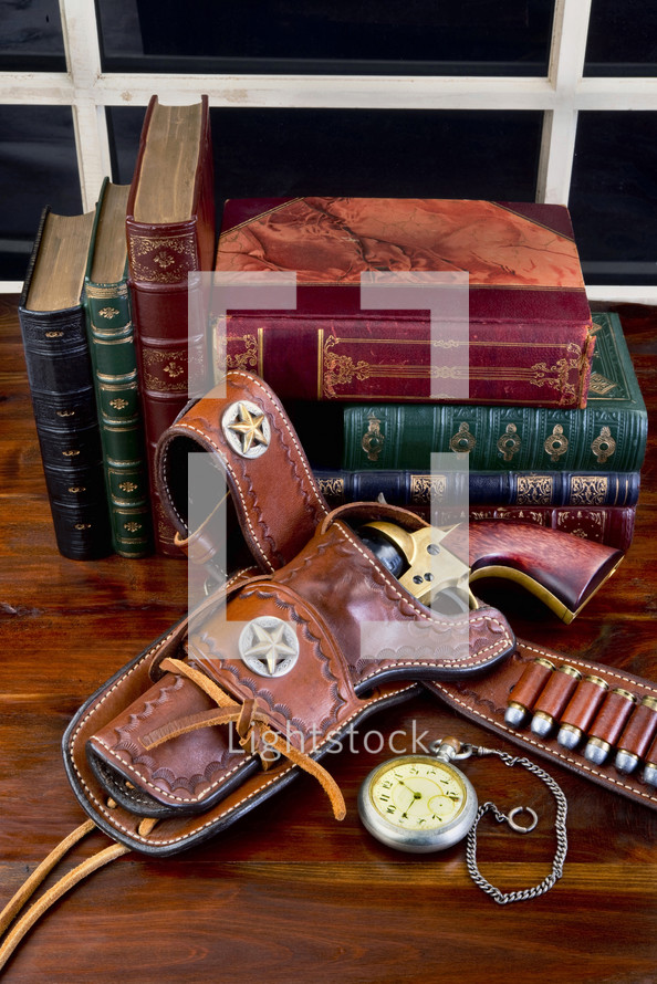 vintage guns in a holster and books on a wood table