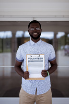 man holding a volunteer signup sheet on a clipboard